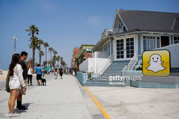 People take pictures in front of the Snapchat Inc headquarters on the strand at Venice Beach in Los Angeles California US on Wednesday Aug 14 2013...