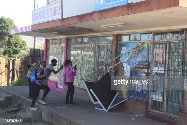 People take pictures of a damaged shop in Mbabane, Eswatini, on June 29, 2021. - Demonstrations escalated radically in Eswatini this week as...
