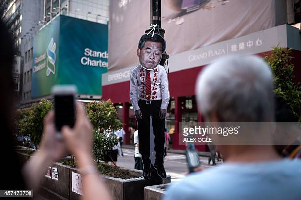 People take pictures of a figure depicting Hong Kong Chief Executive Leung Chunying hanging on a lamppost on a road barricaded by prodemocracy...