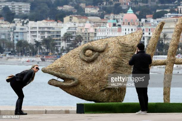 TOPSHOT People take pictures of a giant straw fish created by French sculptor Christian Burger with the collaboration of French sculptors Philippe...