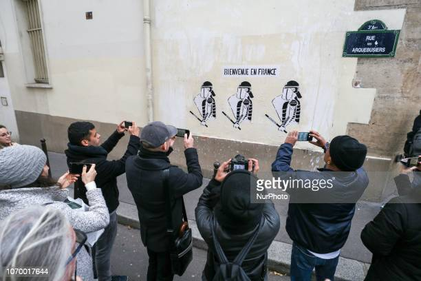 People take pictures of a graffiti showing riot policemen and reading « welcome to France » during a demonstration against rising costs of living in...