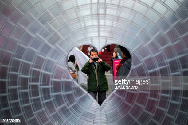 People take pictures of a heartshaped Valentine's Day themed art installation 'Window to the Heart' in Times Square on February 14 in New York PHOTO...