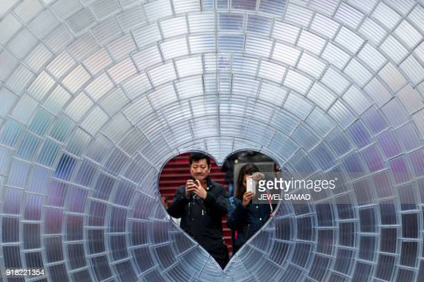 TOPSHOT People take pictures of a heartshaped Valentine's Day themed art installation 'Window to the Heart' in Times Square on February 14 in New...