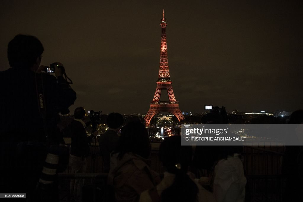 People Take Pictures Of A Light Show On The Eiffel Tower Marking A