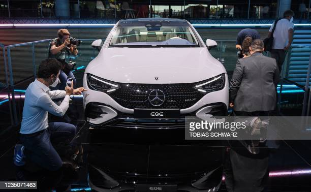 People take pictures of a Mercedes EQE car during the Mercedes-Benz pre-night of the International Motor Show Germany, on September 5, 2021 in Munich.