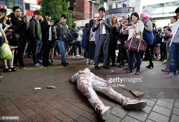 People take pictures of a participant in costume performs to lay down on a ground during Halloween celebration at Shibuya district on October 31 2016...