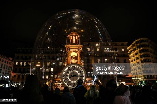 People take pictures of an illuminated monument on December 7 2017 in Lyon during the 19th edition of the Festival of Lights The Festival of Lights...
