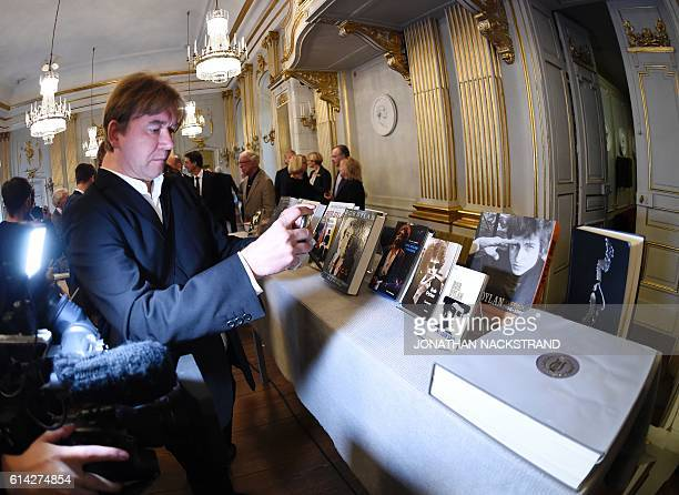 People take pictures of books by US songwriter Bob Dylan who was announced the laureate of the 2016 Nobel Prize in Literature at the Swedish Academy...