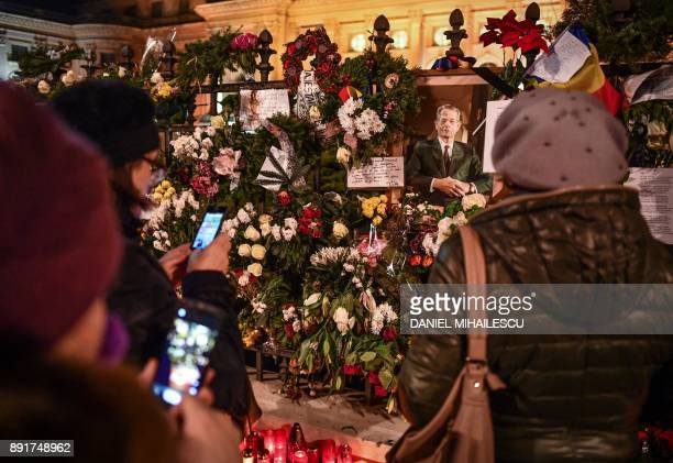 People take pictures of flowers and portraits outside the former Royal Palace that houses the National Arts Museum in Bucharest where the coffin of...
