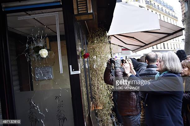 People take pictures of flowers placed in bullet holes in the window of a Japanese restaurant next to the cafe 'La Belle Equipe', Rue de Charonne, in...
