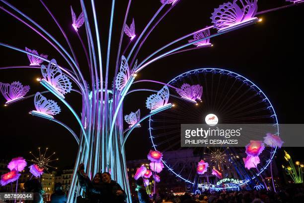 People take pictures of illuminated buildings on December 7 2017 in Lyon during the 19th edition of the Festival of Lights The Festival of Lights...