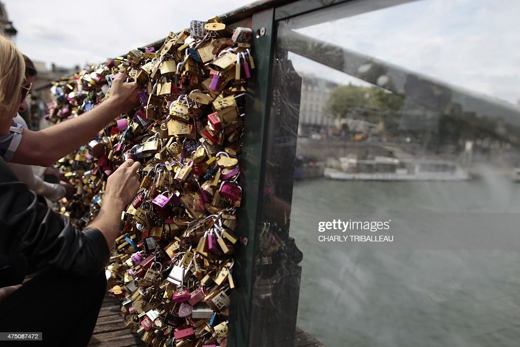 People take pictures of padlocks hanging on the 'Pont des Arts' on May 29, 2015 in Paris as the Paris municipalty announced that the bridge's fences have to be removed due to the weight of the padlocks put by tourists to ensure everlasting love.
