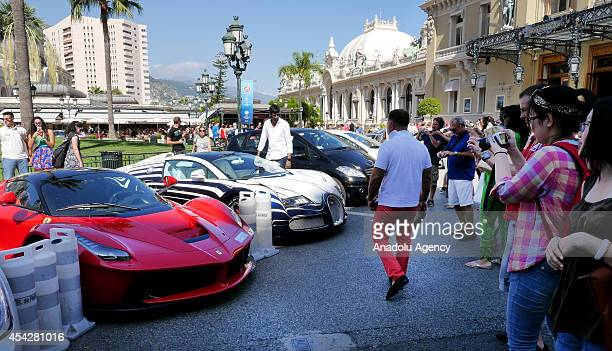 People take pictures of sport cars prior to the UEFA Champions League draw in Monaco on August 27 2014 The 32 clubs 22 of which qualified...