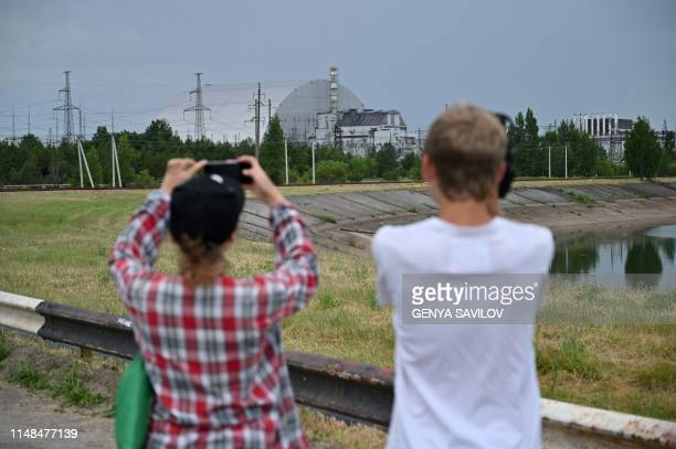 People take pictures of the Chernobyl nuclear plant and Chernobyl's New Safe Confinement covering the 4th block during a tour in the Chernobyl...