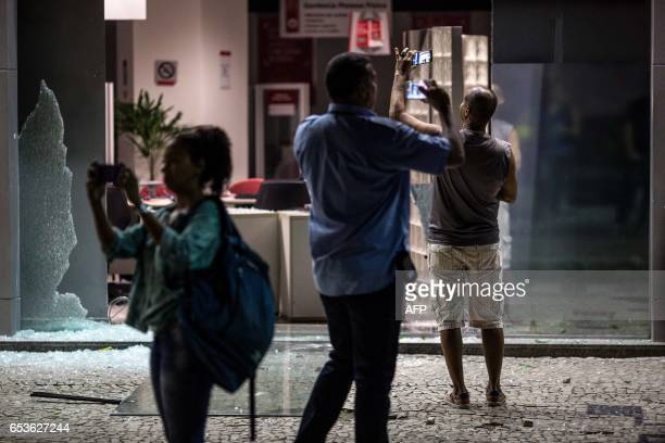 TOPSHOT People take pictures of the entrance of a bank vandalized by protesters during a national strike against the government's social welfare...