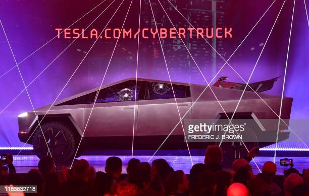 People take pictures of the newly unveiled allelectric batterypowered Tesla's Cybertruck with shattered windows after a failed resistance test at...