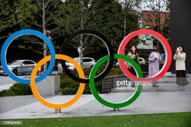 People take pictures of the Olympic Rings outside the closed Japan Olympic Museum in Tokyo on March 27 three days after the historic decision to...