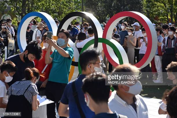 People take pictures of the Olympic rings outside the Olympic stadium in Tokyo, on July 23 ahead of Tokyo 2020 Olympic games opening ceremony.