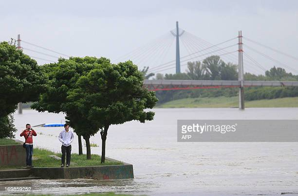 People take pictures of the overflooding shores of the Danube river in Vienna on June 3 2013 Much of the western provinces of Vorarlberg Tyrol and...
