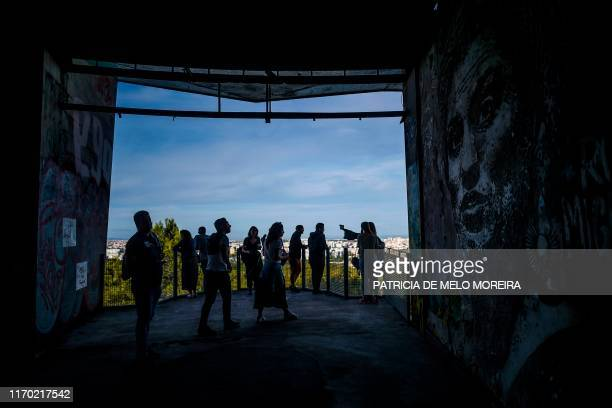 People take pictures of the panoramic view of Lisbon and of Portuguese artist Vhils' artwork in memory of Brazilian activist Marielle Franco at the...