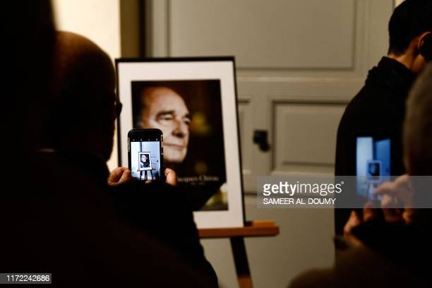TOPSHOT People take pictures of the portrait of former French President Jacques Chirac during a memorial ceremony at the SaintLouisdesInvalides...
