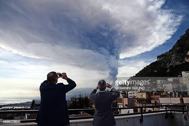 People take pictures of the smoke rising over the city of Taormina during an eruption of the Mount Etna one of the most active volcanoes in the world...