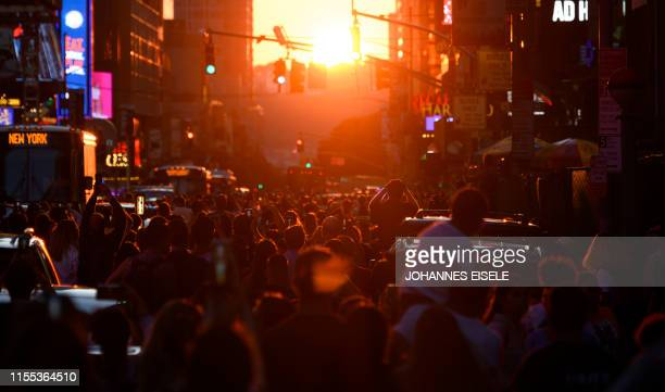 People take pictures of the sun setting over Manhattan on 42nd Street during the so called Manhattanhenge on July 12 2019 in New York City...