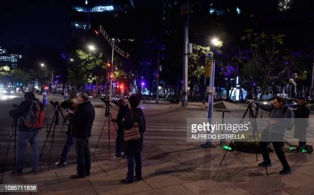 People take pictures of the Super Moon during the start of the total lunar eclipse at the Angel de la Independencia in Mexico City on January 20 2019