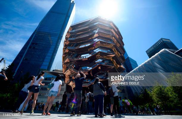People take pictures of the Vessel at Hudson Yards on a sunny day on May 18, 2019 in New York City. - After a cold and rainy weather, the National...