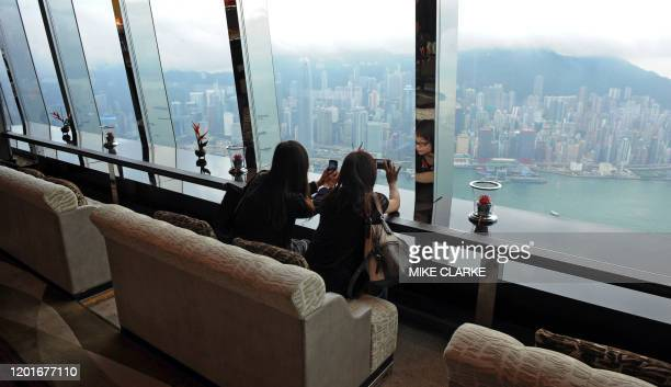 People take pictures of the view from the 102nd floor of the Ritz-Carlton hotel in Hong Kong on May 3, 2011. Towering some 490 metres above the...