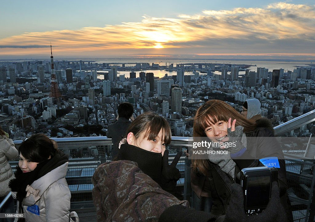 People take pictures of themselves with the sunrise on New Year's Day at the open-air Sky Deck of Roppongi Hills, some 238 metres (780 ft.) above ground level in Tokyo on January 1, 2013