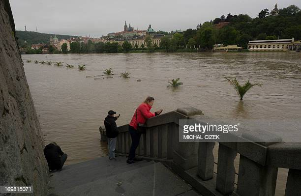 People take pictures of tree tops peeping out from the flooded river bank of Vltava river on June 02 2013 in Prague After another night of downpours...