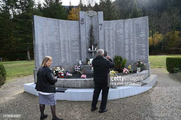 """People take pictures on October 29 in Saint-Laurent-du-Pont, south-east France, at a memorial in tribute to the 146 victims of a fire in the """"5-7""""..."""