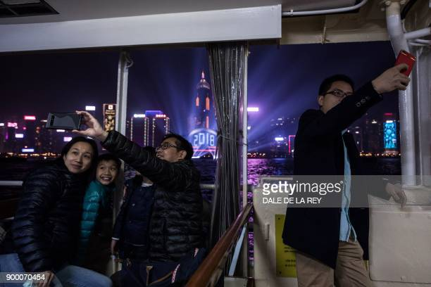 People take pictures onboard the Star Ferry as they cross Victoria harbour ahead of New Year celebrations in Hong Kong on December 31 2017 / AFP...