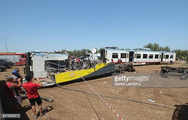 People take pictures using mobile devices of the train crash site on July 13 2016 near Corato in the southern Italian region of Puglia as rescuers...