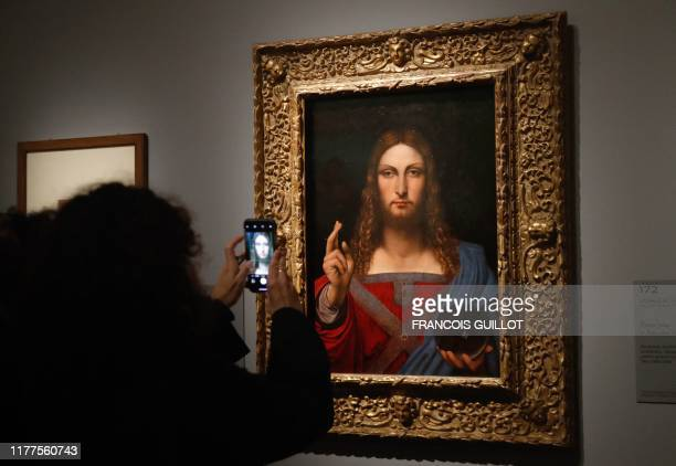 People take pictures with a mobile phone of an oil painting by Atelier Leonardo da Vinci's Salvator Mundi during the opening of the exhibition...