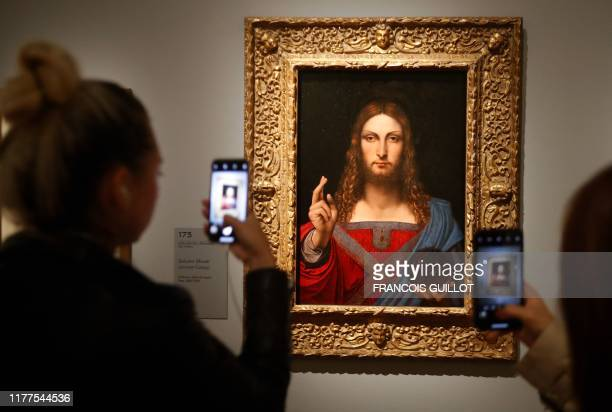 TOPSHOT People take pictures with mobile phone at an oil painting by Atelier Leonardo da Vinci's Salvator Mundi during the opening of the exhibition...