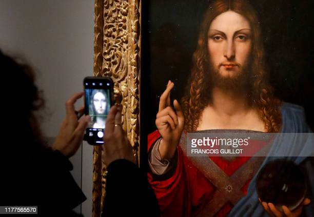 People take pictures with mobile phone of an oil painting by Atelier Leonardo da Vinci's Salvator Mundi during the opening of the exhibition Leonardo...