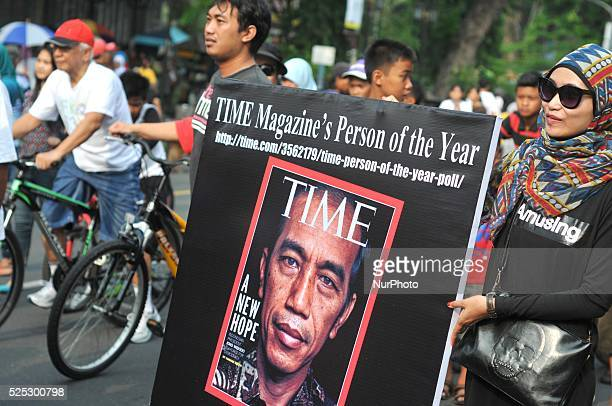 People take pictures with posters of the cover of TIME magazine during a promote Indonesian President Joko Widodo in the voting of quotPerson in The...