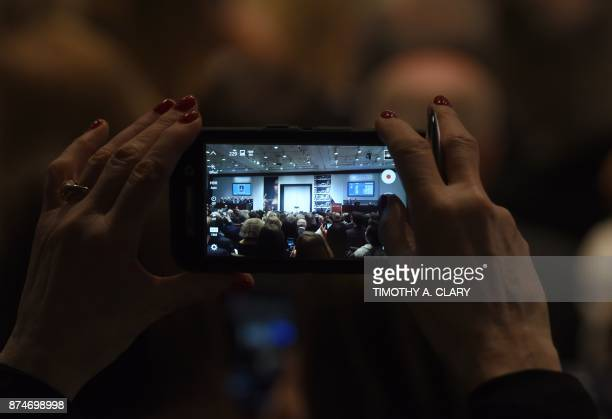 People take pictures with their cellphones at Christie's where bidding for Leonardo da Vincis 'Salvator Mundi' is being sold at auction at Christie's...