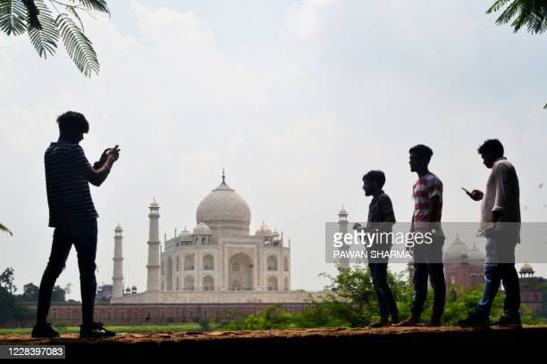 People take pictures with their mobile phones near the Taj Mahal in Agra on September 8, 2020. - India's top tourist attraction the Taj Mahal is set...