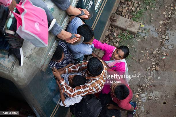 People take risks and try to climb onto the roof of the train to travel to their villages in Dhaka Bangladesh July 16 2015 Muslim Homebound people...