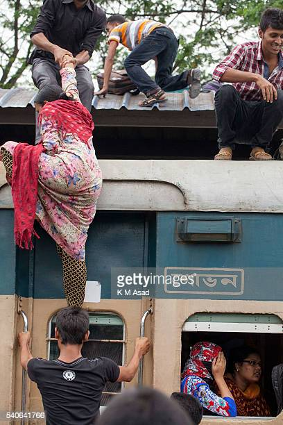 People take risks and try to go to the roof of the train to travel to their villages in Dhaka Bangladesh July 16 2015 Muslim Homebound people crowd...
