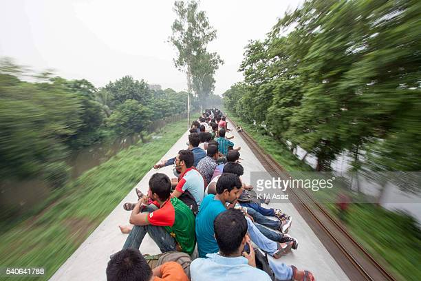 People take risks to travel on the roof top of the train to go their villages from Dhaka Bangladesh July 16 2015 Millions of Bangladeshis are...