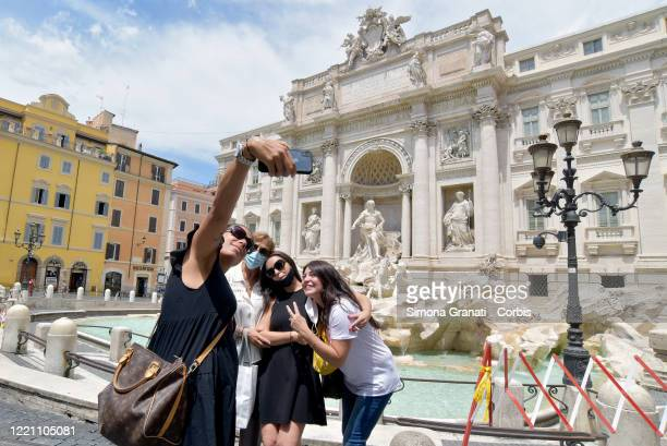 People take selfies in front of Trevi Fountain on June 19, 2020 in Rome, Italy. Italy has reopened its major tourist attractions and loosened travel...