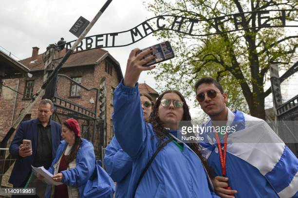 People take selfies outside 'Arbeit Macht Frei' sign near the main entrance gate to Auschwitz I. Under the theme 'Say No To Anti-Semitism' over...