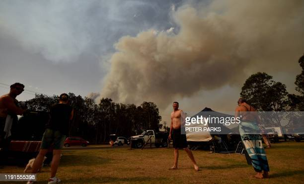 People take shelter by the beach as a bushfire burns in Batemans Bay in New South Wales on January 4, 2020. - Up to 3,000 military reservists were...