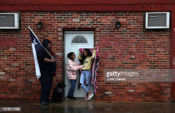 People take shelter from the rain as they wait for the train carrying the casket of former US President George HW Bush to the George HW Bush...