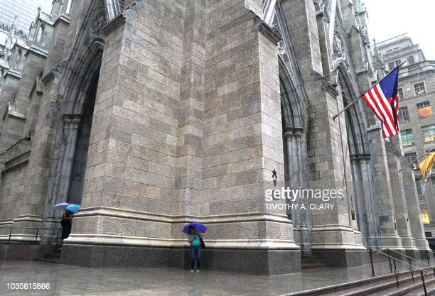 People take shelter outside St Patrick's Cathedral as the remnants of Hurricane Florence hit the New York City area on September 18 2018