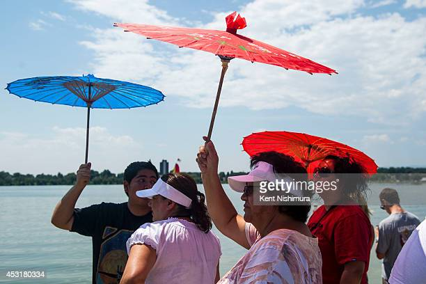 People take shelter under parasols while watching the Dragon Boat Races during the 2014 Colorado Dragon Boat Festival at Sloans Lake Park on Sunday...